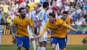 FC Barcelona's Lionel Messi, right, reacts next to teammate Arda Turan after scoring against Malaga during a Spanish La Liga soccer match between Malaga and FC Barcelona at La Rosaleda stadium in Malaga, Spain, Saturday, Jan. 23, 2016. (AP Photo/Daniel Tejedor)
