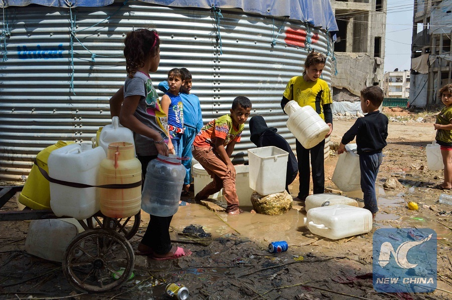 (150804) -- ALEPPO, Aug. 4, 2015 (Xinhua) -- Syrian children fill plastic containers with drinking water in Aleppo city, Syria, on Aug. 4, 2015. Child labor has become rampant in Aleppo. Children in Aleppo are increasingly working on collecting plastic and hard paper to sell in order to help their conflict-weary parents. (Xinhua/Abd Fayad)