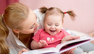 happy mother read a book to child girl indoors
