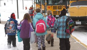 Tribune photo by Ron Adams (010314-bus-kids-01-03)  Students from Prairie Woods Elementary in New London stay warm in their snow-pants, parkas and boots as they scurry to their buses Friday afternoon where they were leaving for an extended weekend due to the weather.